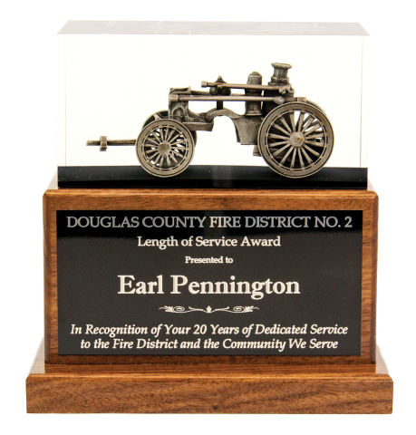Antique steam fire pumper embedded in clear acrylic, mounted on solid walnut base