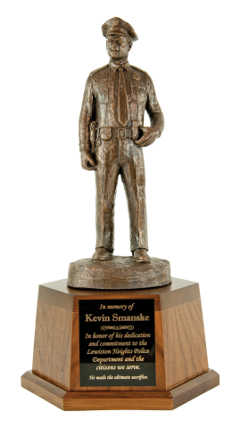 Statue of a police officer standing at attention cast in bronze.