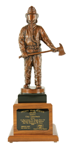 Bronze finished firefighter, cast resin with axe, mounted on sold walnut base with engraved plate.